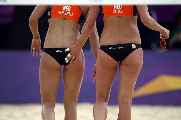 Sanne Keizer congratulates teammate Marleen van Iersel after scoring a point during their women's beach volleyball preliminary round match against